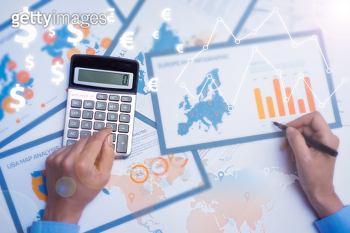 Business analyst doing paperwork with financial analysis graphs