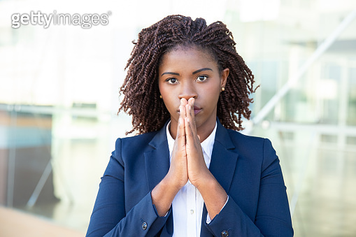 Young businesswoman praying and looking at camera