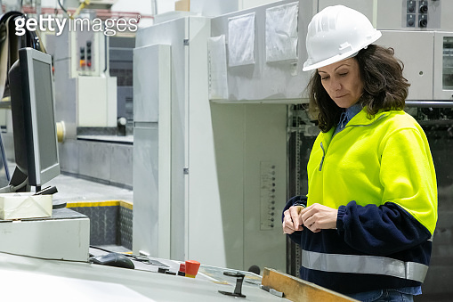 Serious focused machine operator standing at workplace