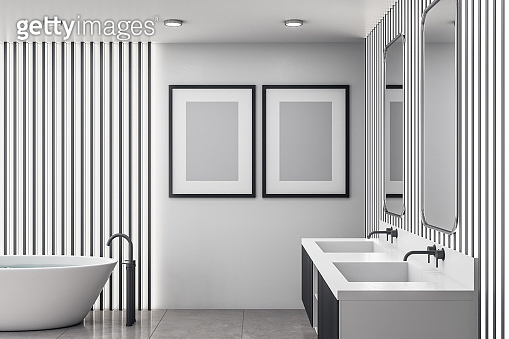 Bathroom interior with white bath and two poster on wall.