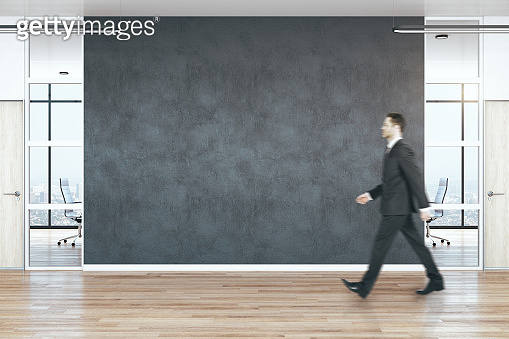 Businessman walking in modern empty office hall