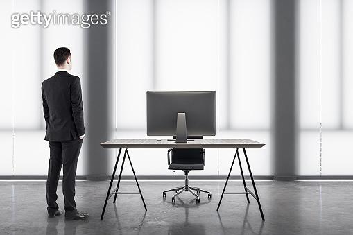 Businessman standing in minimalistic office interior