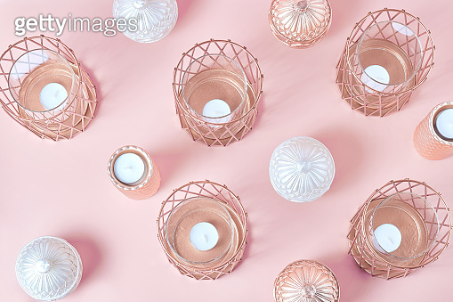 home decor in the form of candles and candlesticks in rose gold. flat lay, pink background