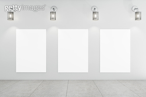 Modern gallery interior with three blank poster on wall.