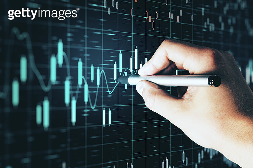 Businessman hand drawing at stock chart on virtual screen interface. T