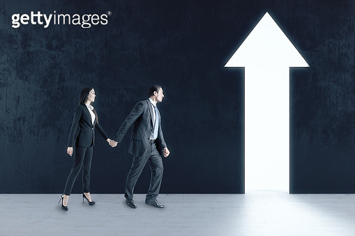 Businessman and businesswoman walking to abstract white arrow
