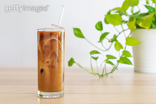 cold brew coffee with milk on white wooden table.
