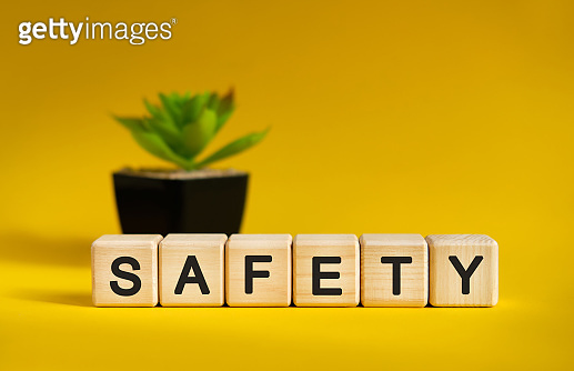 SAFETY - business financial concept on a yellow background. Wooden cubes and flower in a pot.