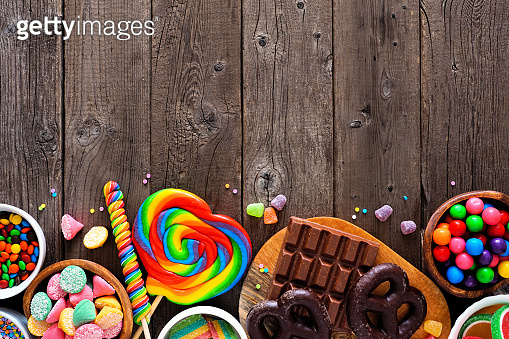 Sweet and colorful candy buffet bottom border, top view table scene over a rustic wood background