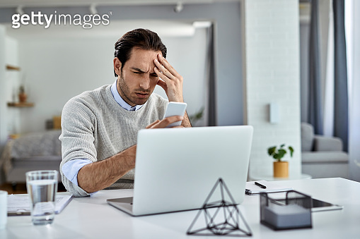 Young businessman having a headache while reading bad news over mobile phone at home.