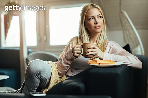 Beautiful woman day dreaming while drinking coffee at home.