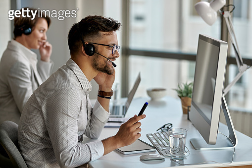 Happy call center agent using computer while communicating with clients  in the office.