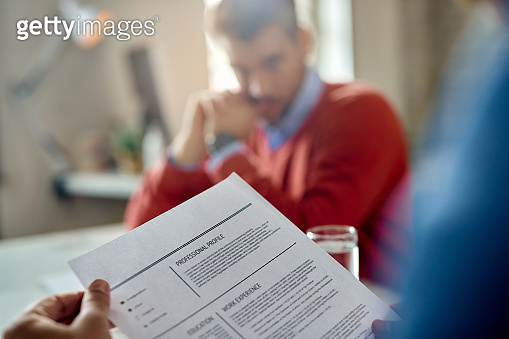 Close-up of a businessman reading candidate's resume during a job interview.