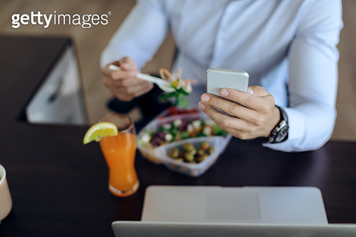Close-up of businessman using smart phone during lunch break.