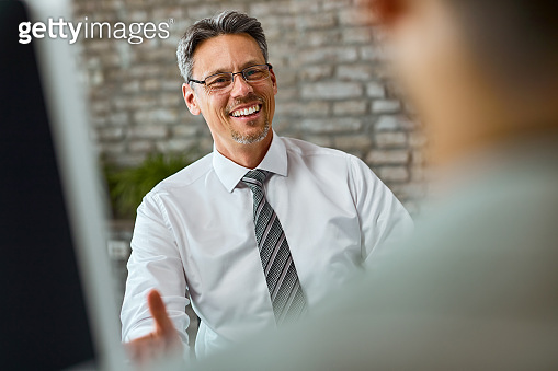 Happy businessman talking to his colleague in the office.