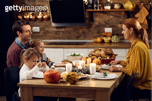 Happy family enjoying in Thanksgiving dinner at dining table.