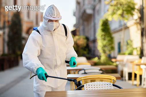 Healthcare worker in hazmat suit disinfecting sidewalk cafe during COVID-19 epidemic.