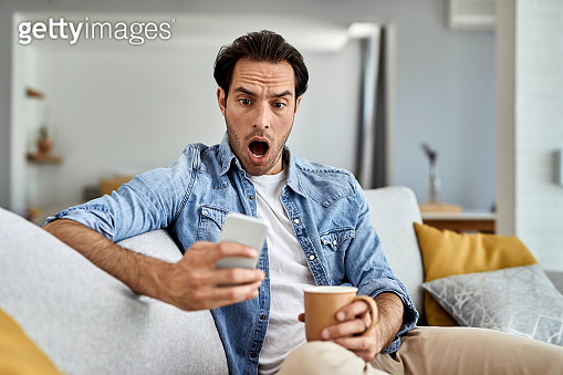 Young shocked man reading text message on mobile phone at home.