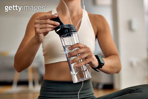 Unrecognizable female athlete having a water break while working out at home.