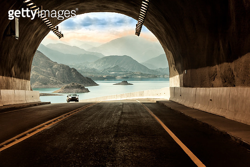 Tunnel in the Pan-American Route of Argentina - Chile, in the background Lake Potrerillos at sunset, Mendoza, Argentina.