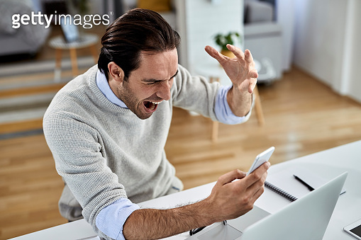 Frustrated businessman screaming while reading problematic text message on mobile phone.