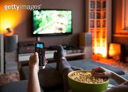 Woman relaxing at home watching tv and eating popcorn