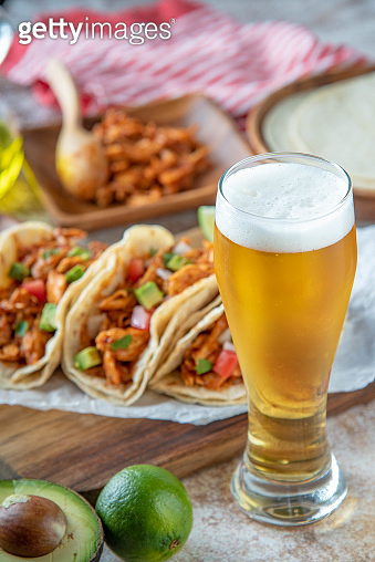 shredded chicken tacos with glass of beer