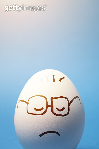 Drawing of Sad Facial Expression on an Egg with Blue Background