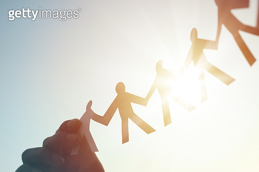 Hands Holding Paper Human Chain in the Sky Against Sunlight and Blue Sky