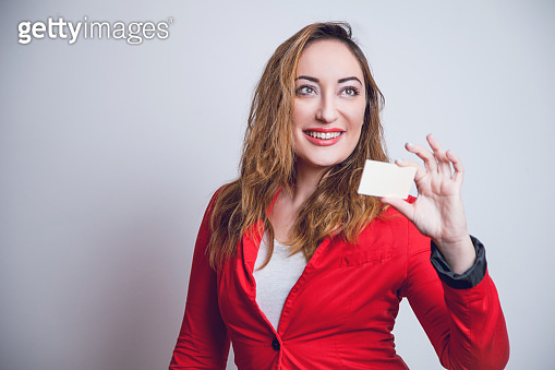 Excited young woman holding credit card