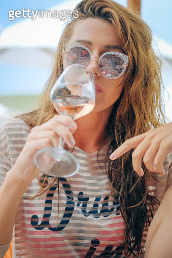 Young elegant woman relaxing with wine on a vacation
