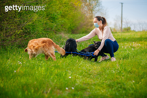 Woman wearing a protective mask walking  with a dogs outdoors