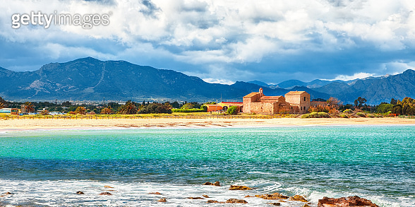 The Nora bay and beach, the medieval Sant'Efisio church near the shore and mountains in the background.