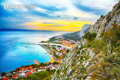 Beautiful aerial panoramic view of Cetina river, mountains and Old town Omis at sunset