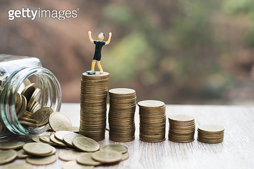 The coin ladder has a businessman. business and saving money concept.Tiny businessman figure standing on stack of coin. Money and financial concepts.Financial, Business planning and Growth concept.