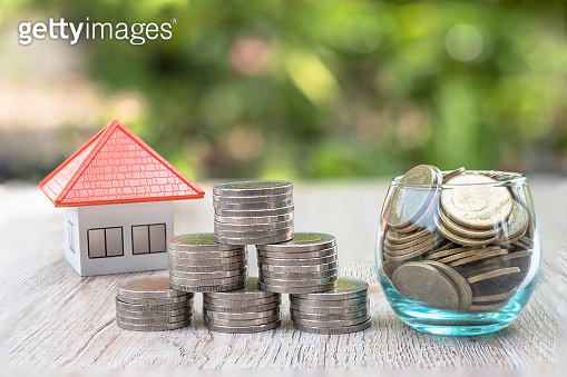 The orange roof house near the coin in a glass bottle Ideas to save money, buy a house and mortgage, real estate and invest, buy a house, rental tax, sales.