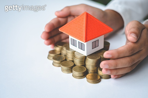 Orange roof houses are put on piles of coins and have hands protecting near the idea.Saving money for home purchases or loans for real estate investment planning and ideas during savings can be risky.