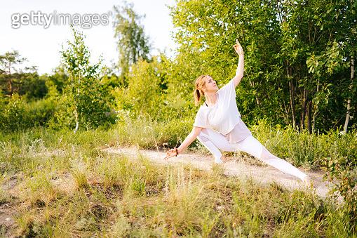 Young yogi woman practicing yoga on park outside the city. Meditative lady enjoying meditation