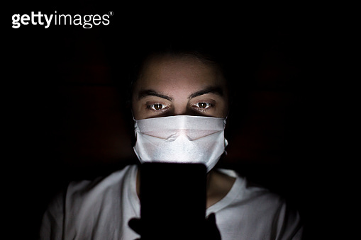 Man using smart phone at night with Dark House and light on his Face with Mask