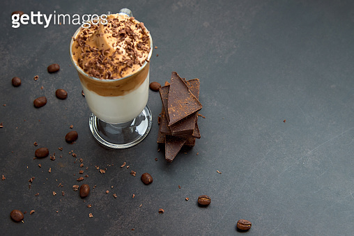 Glass of trendy fluffy creamy dalgona or whipped instant coffee with milk, coffee beans and chocolate on the dark background. New popular food and drink trend concept. Copy space.