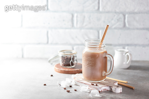 Ice coffee with milk and ice in a glass jar on a light background. Bamboo drinking straws with Zero - waste. Glass mason jar.