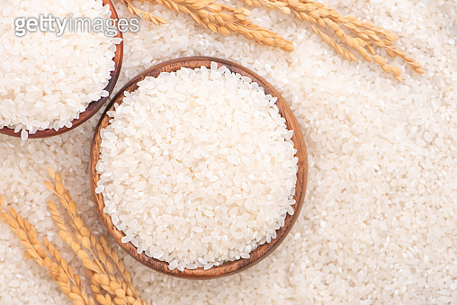 Raw rice in a bowl and full frame in the white background table, top view overhead shot.