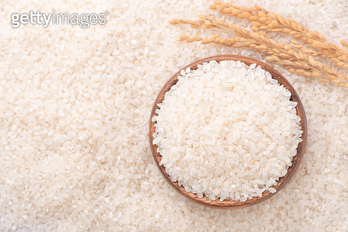 Raw rice in a bowl and full frame in the white background table, top view overhead shot, close up