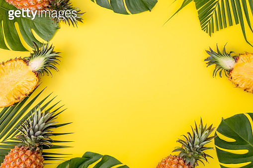 Beautiful pineapple on tropical palm monstera leaves isolated on bright pastel yellow background, top view, flat lay, overhead above summer fruit.