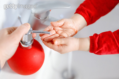 Closeup of little toddler girl washing hands with soap and water in bathroom. Close up child learning cleaning body parts. Hygiene routine action during viral desease. kid at home or nursery.