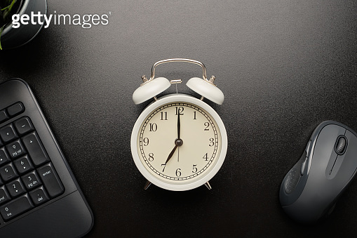Vintage alarm clock in white color is between black keyboard and mouse on black working table. View from the top of the desk with the white vintage alarm clock in the center of the image.