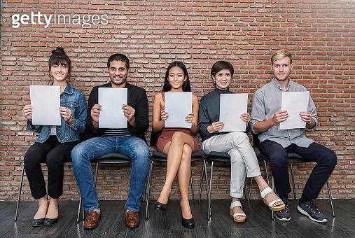 Portrait of happy young asian caucasian business people waiting for job interview hands holding white paper. Group Of People Sitting On Chair In A Waiting Room. Competitive lifestyle concept
