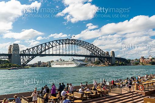 People enjoy the view of sydney harbour bridge at outdoor restaurants in Circular Quay in Sydney, Australia