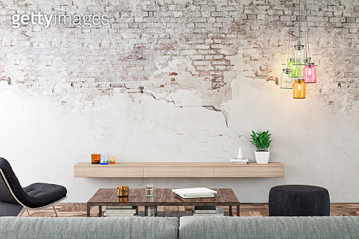 Empty nostalgic living room with gray sofa, lounge chair, pouffe, table and decoration in front of ruined brick wall stock photo