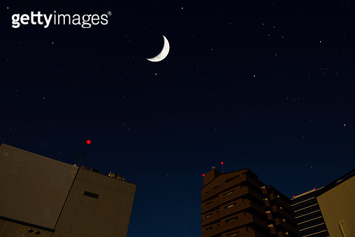 Crescent moon rising over the buildings